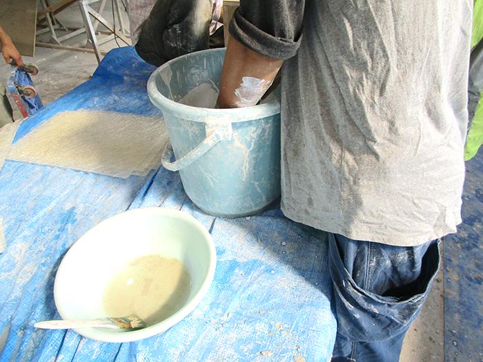 バケツで石膏を作っている男性