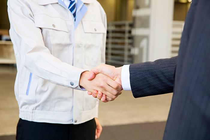 作業着の男性とスーツの男性の握手